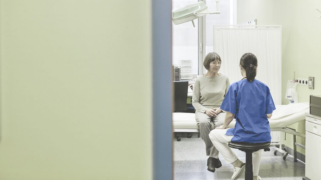 a person is sat on a hospital bed talking to a healthcare staff member wearing a blue uniform