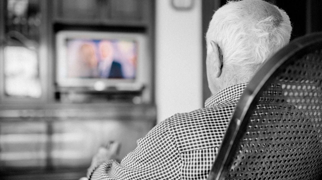 senior watching TV seen from behind