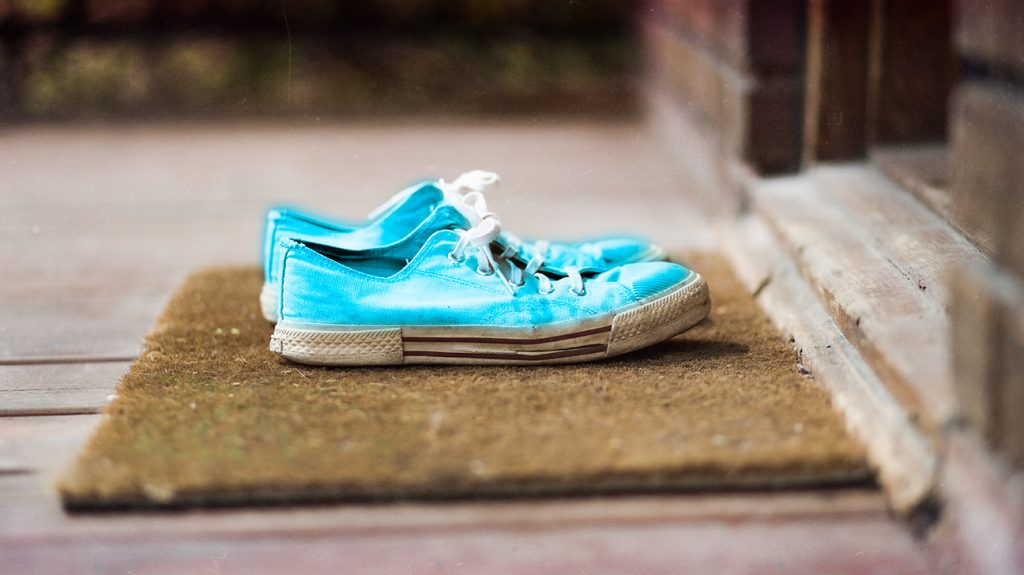 sports shoes left on a doormat