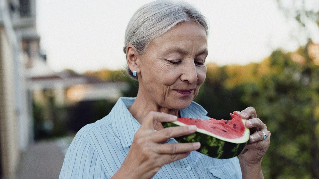 a person wearing a blue shirt is in a garden eating a slice of watermelon