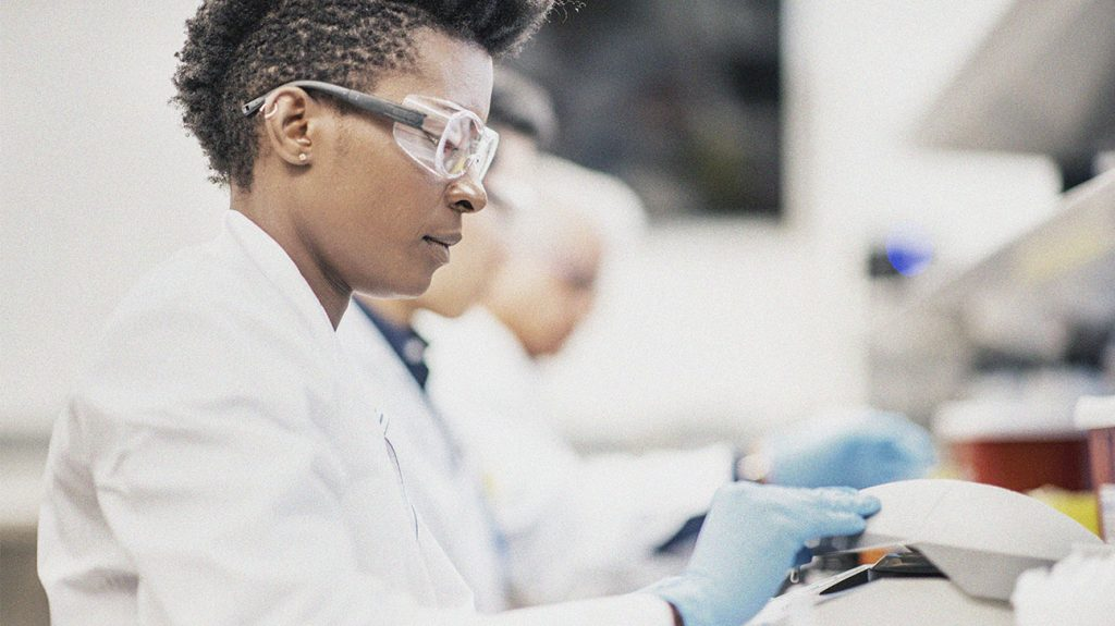 a scientist wearing a white coat and blue gloves is working in a lab