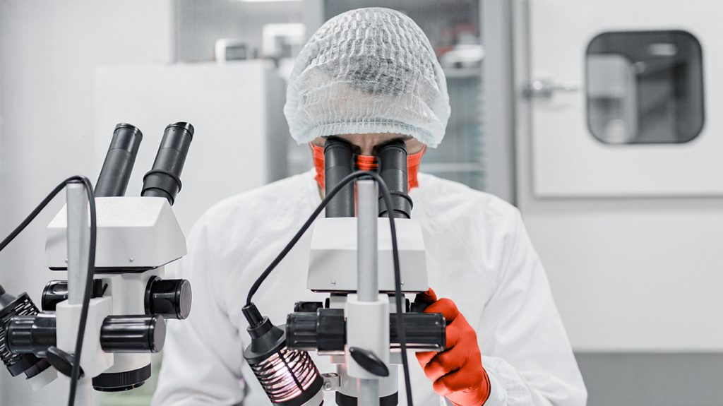 scientist wearing PPE in lab looking through a microscope