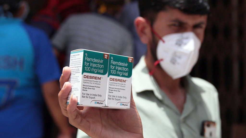 Someone wearing a fact mask holding boxes of remdezivir