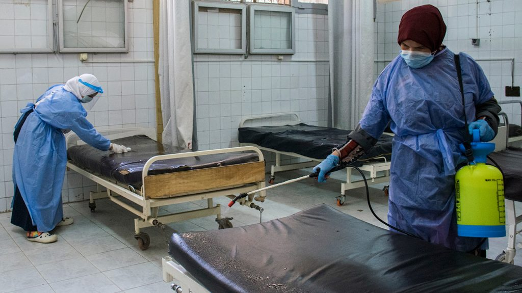 people wearing PPE cleaning hospital beds