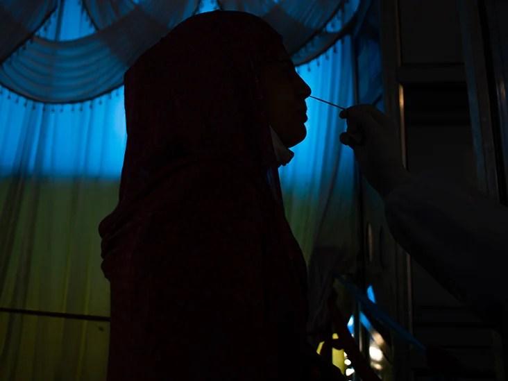 克什米尔穆斯林女孩被剪影,因为卫生官员使用鼻牌来收集她的样本来对冠状病毒病进行测试