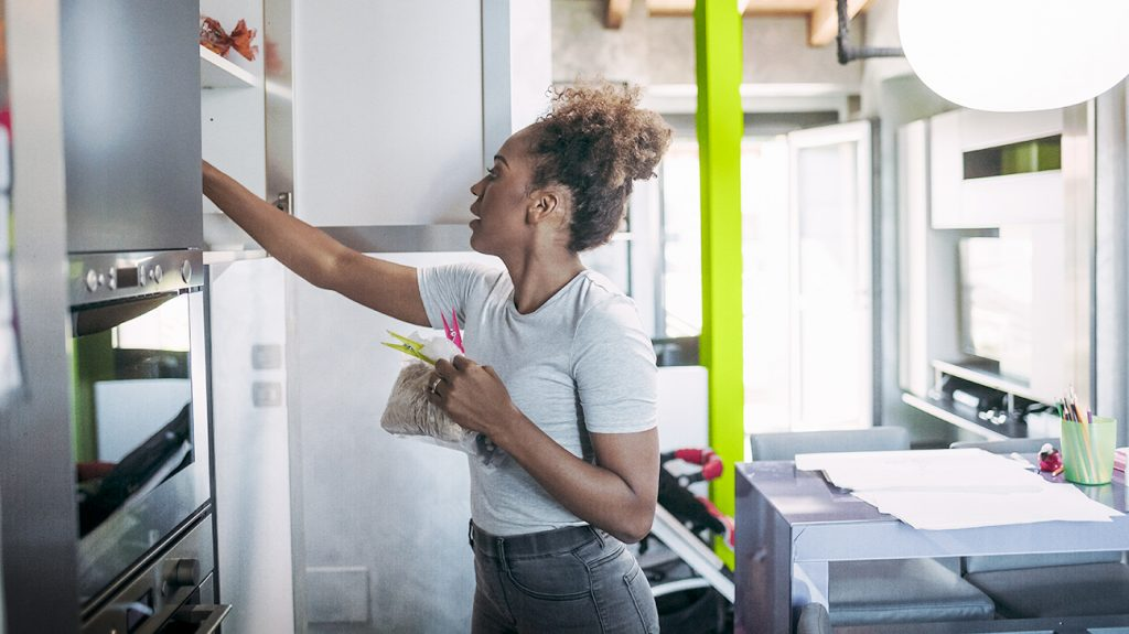 a woman reaches up into a kitchen cabinet