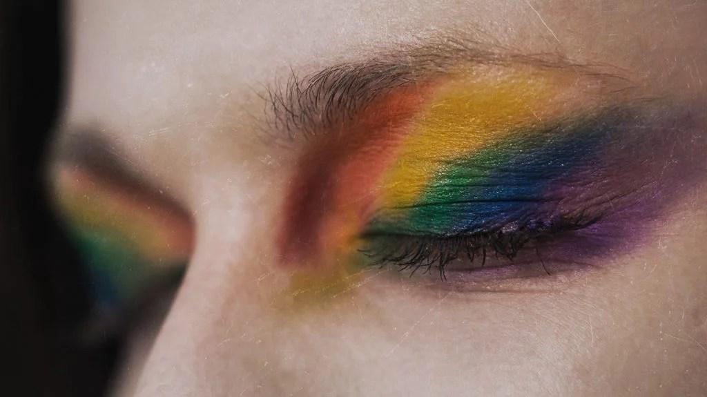 关闭一个人的眼皮与构成彩虹旗子的颜色