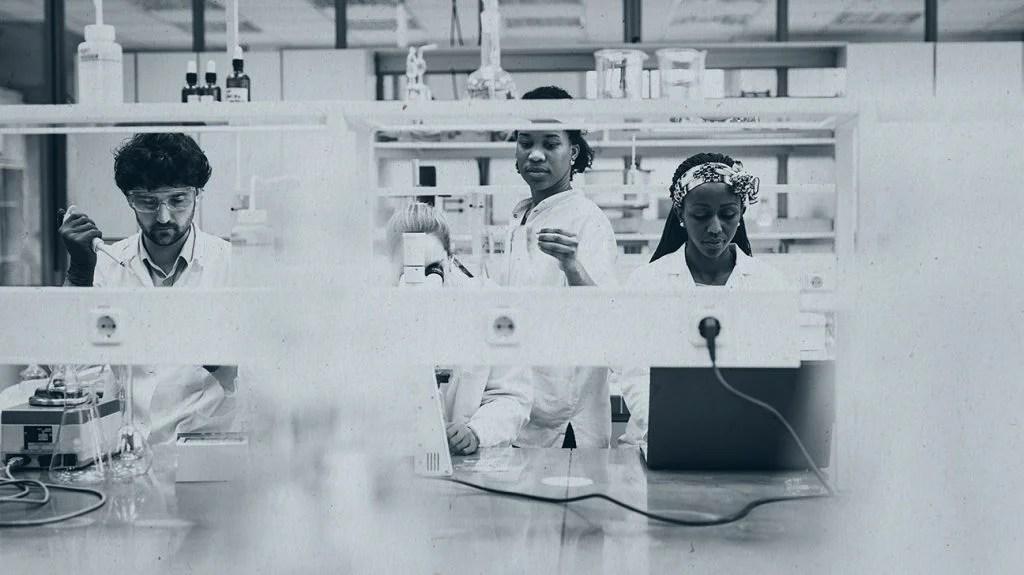 在实验室工作的黑研究员的黑白图象
