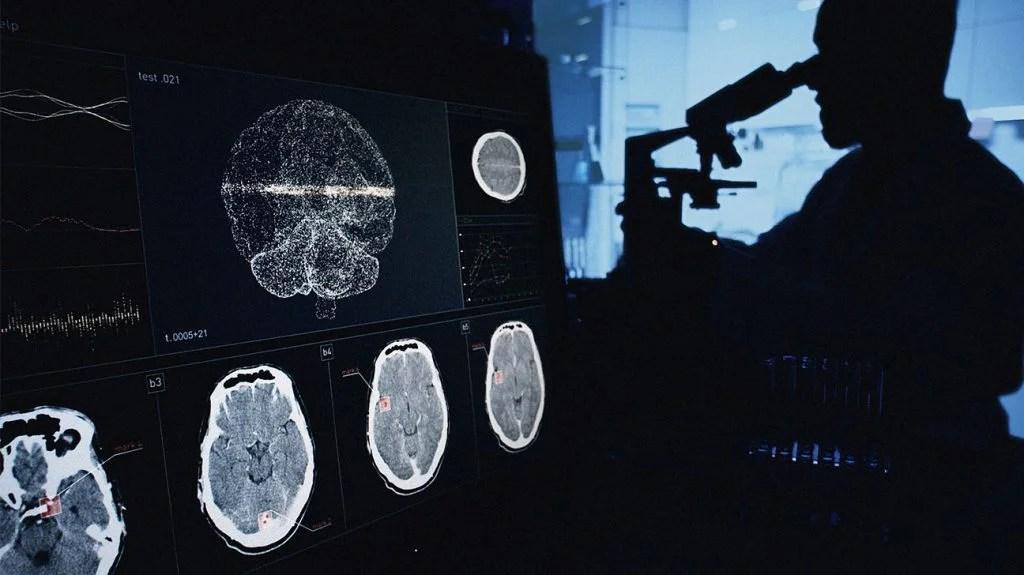 一位科学家正用显微镜在电脑屏幕上观察脑电波扫描研究