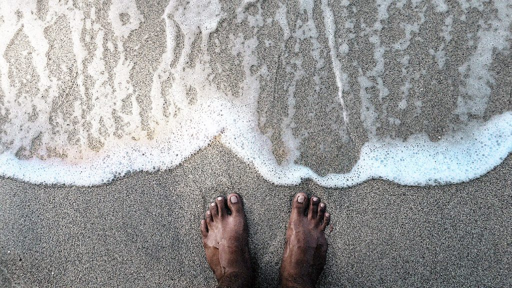 close up of a person's feet on a shore with waves coming up