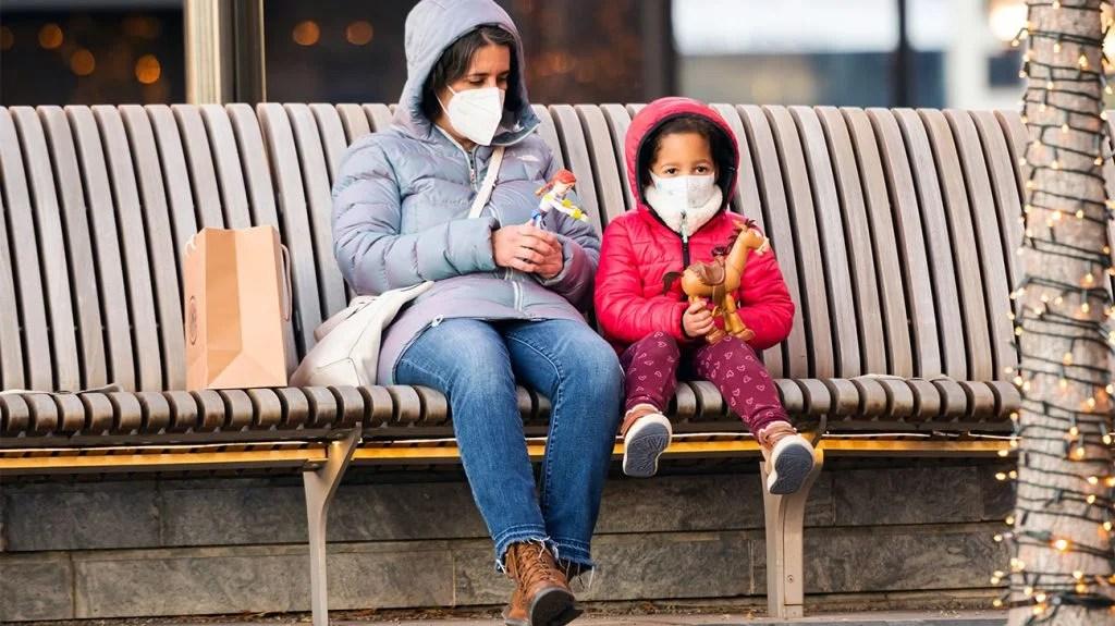 母亲和孩子在公共汽车站戴着面具