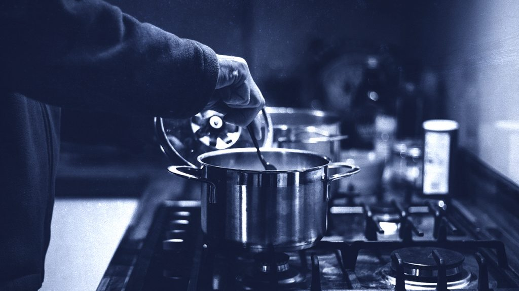 close up of hand cooking food on stove