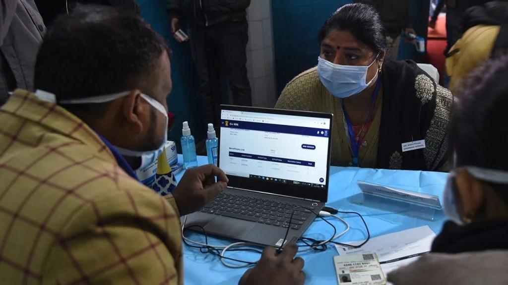 在印度的人们试图在他们的笔记本电脑上预订疫苗