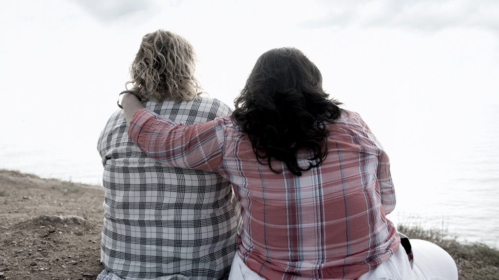 two people with obesity hugging seen from behind