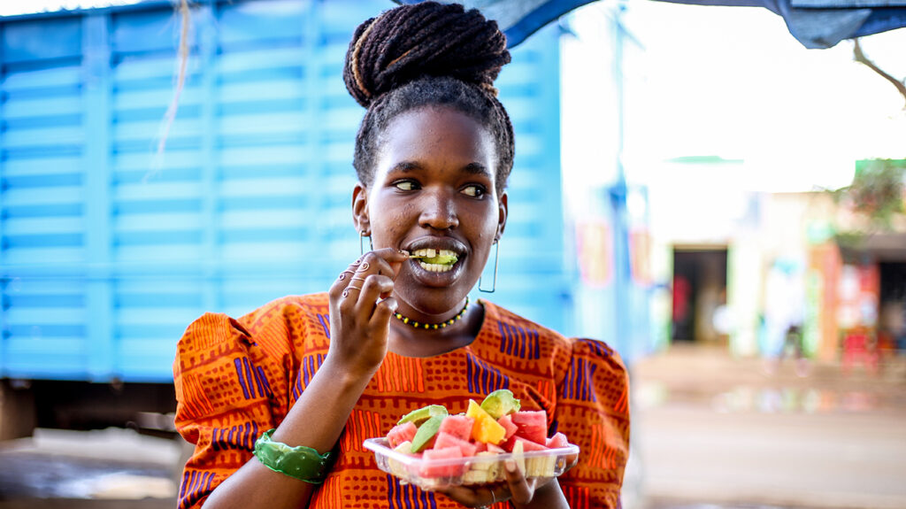 A person practicing intuitive eating snacks on fruit.