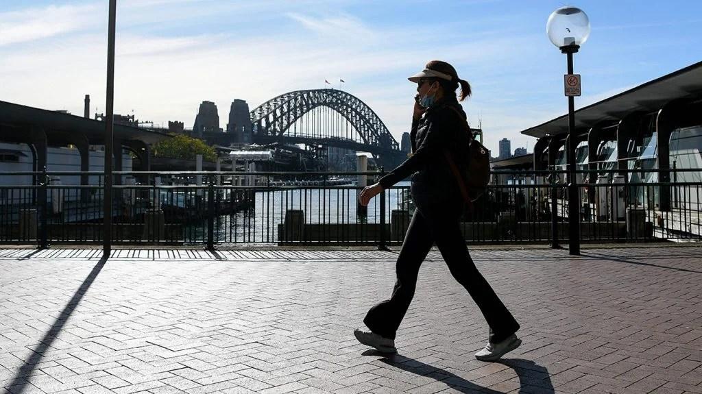 穿面部面具的女人走过一座桥。