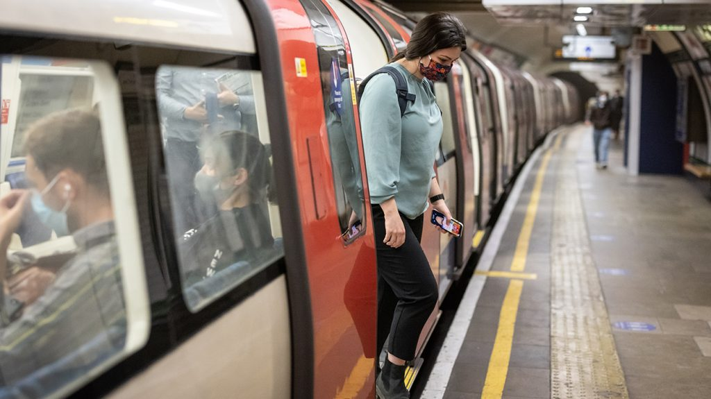 A woman with a mobile phone in her hand steps off an underground onto the platform