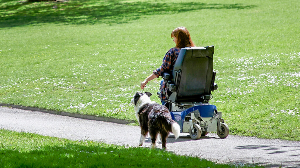 Disabled-woman-taking-dog-for-walk-in-park