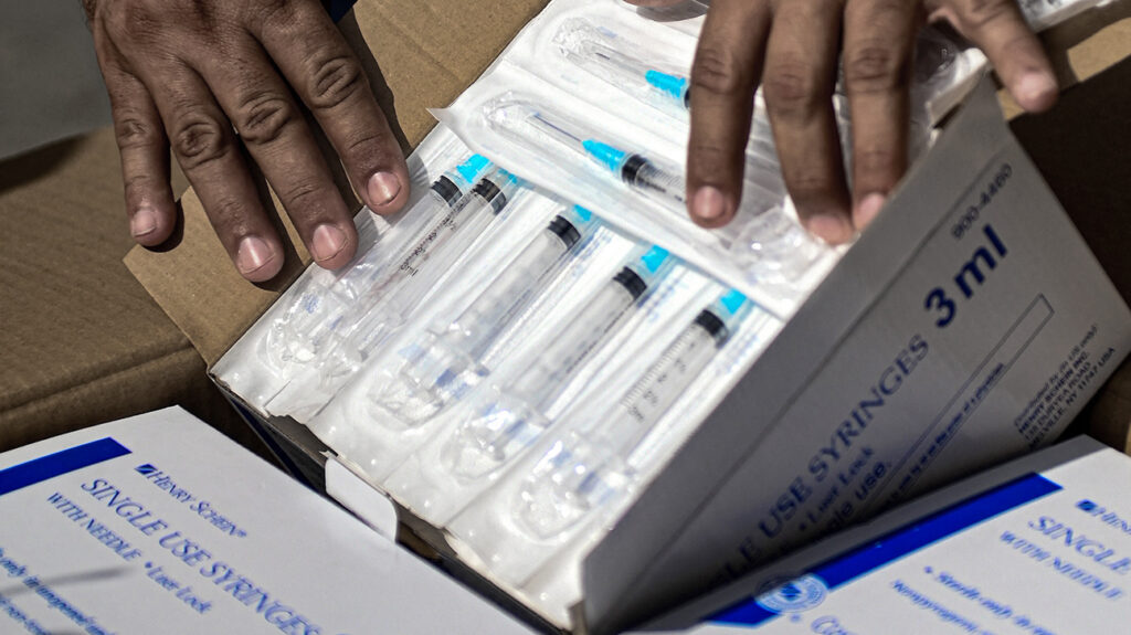 A healthcare worker in Havana, Cuba opens a box of donated syringes sent by Cuban solidarity groups based in the United States on July 23, 2021