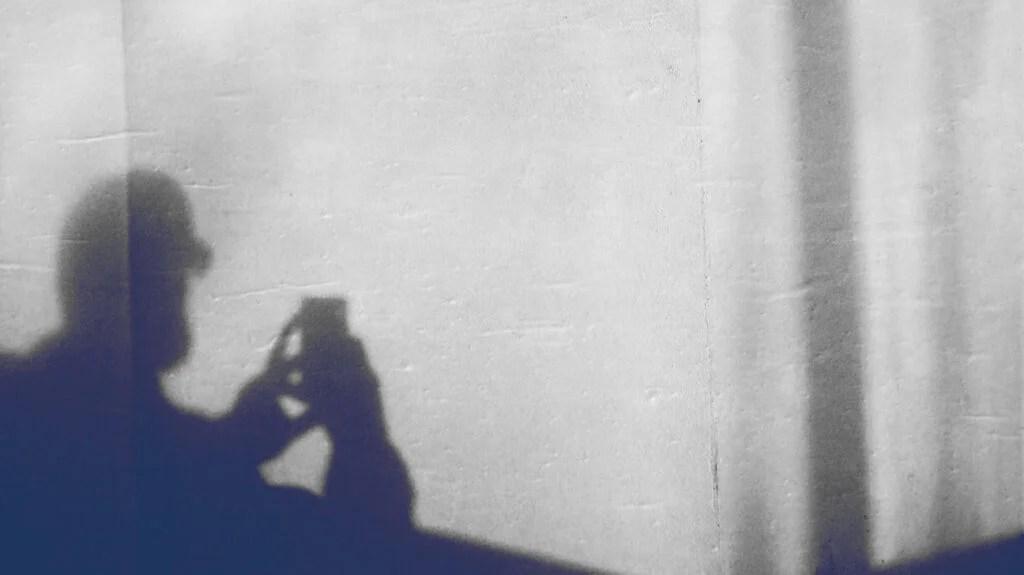 Quelqu'un utilisant un smartphone projette une ombre sur un mur