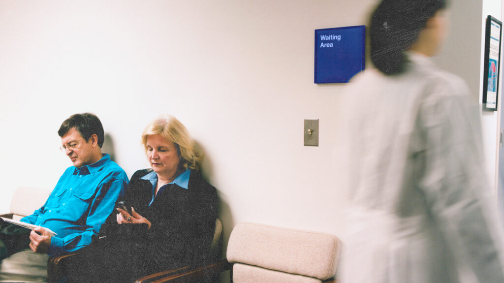 A male and female in a hospital waiting room who may have breast cancer.