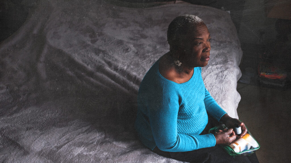 older woman looking confused sitting on a bed