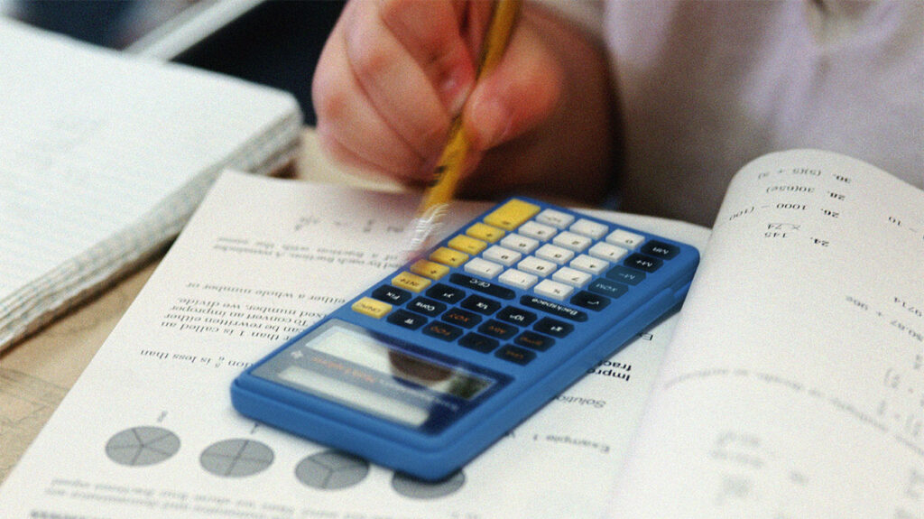 A child presses the buttons of a calculator with a pencil to solve problems in a math book.