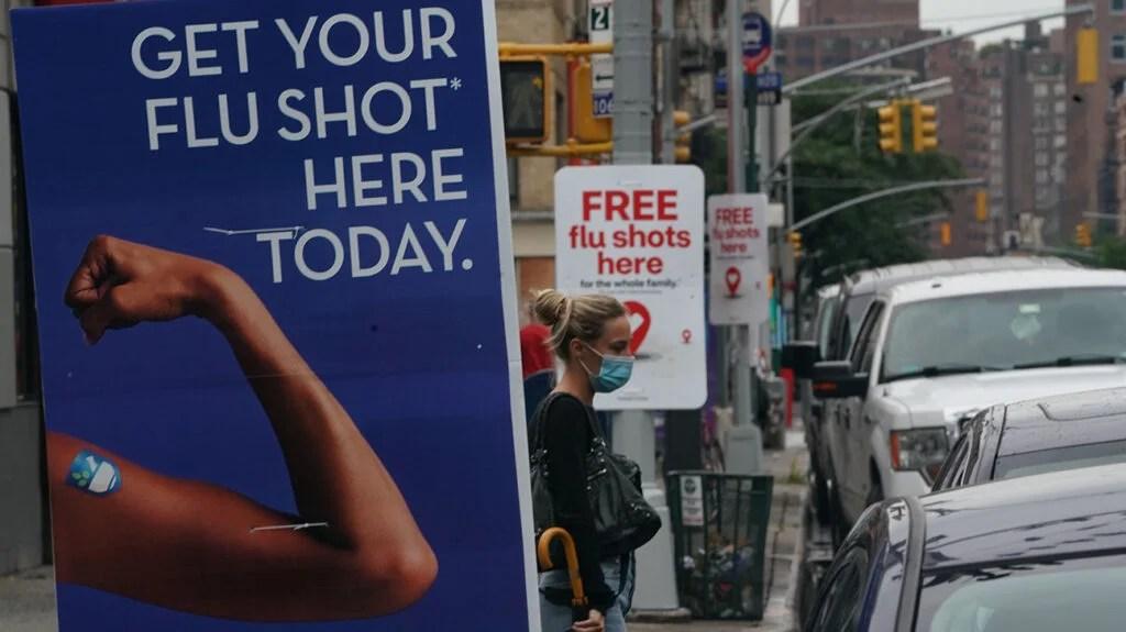 woman wearing mask waiting to cross street among banners offering flu shots