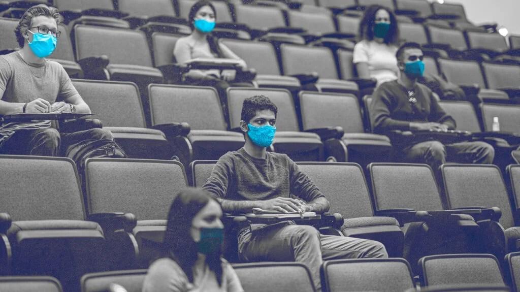 学生们坐在教室里,与教室保持着距离