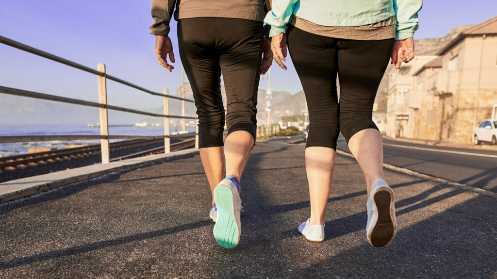 Rear-view-shot-of-two-senior-female-legs-walking-together