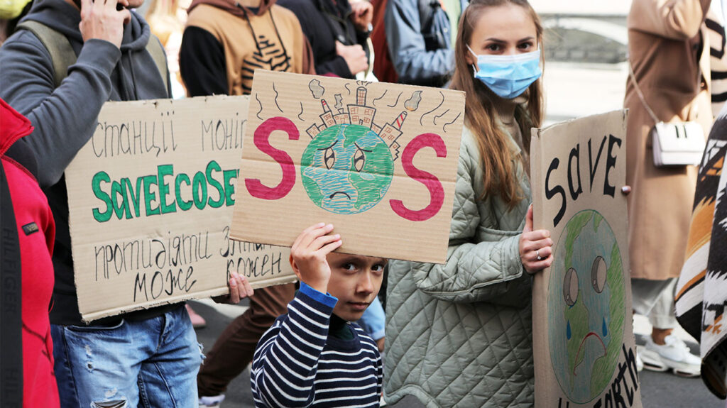 Young people carry placards during a climate change march in Kyiv, Ukraine, September 26, 2021