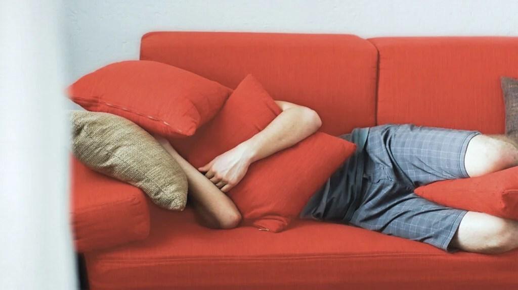 有人在红色靠垫下的沙发上睡着了