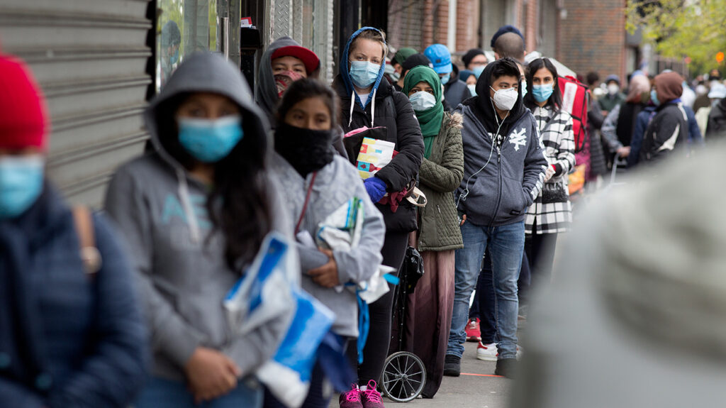 people standing in line with masks on