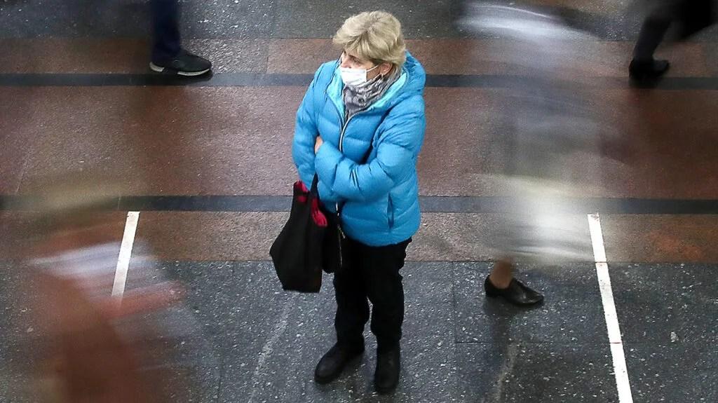 俄罗斯一名妇女戴着口罩在过境途中等候