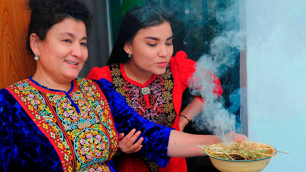 """Turkmen women wearing traditional dress demonstrate how to fumigate a house with the smoke of burning wild rue (known locally as yuzerlik) in Ashgabat on December 11, 2020. – In tightly-controlled Turkmenistan, which still insists it has no virus cases, the pandemic has led to a boom in a herb whose Turkmen name translates as """"medicine for a hundred illnesses"""". Wild rue — known locally as yuzerlik — has for millennia been popular in North Africa, the Middle East and Central Asia as a panacea for sickness and ill fortune. But in Turkmenistan strongman leader and ex-dentist Gurbanguly Berdymukhamedov has gone a step further. In March he ordered wild rue burning on a """"systematic level"""", trumpeting the bacteria and infection-killing qualities of its faintly intoxicating smoke. (Photo by Igor SASIN / AFP) (Photo by IGOR SASIN/AFP via Getty Images)"""