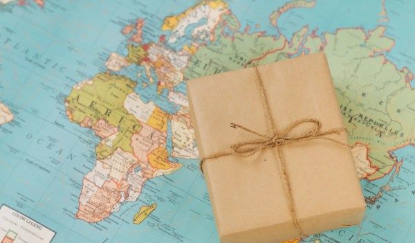 International shipping. Cardboard box on the geographical map background