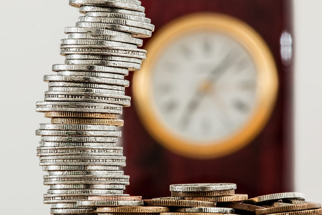 blurry clock in the background with a stack of coins in focus in the front