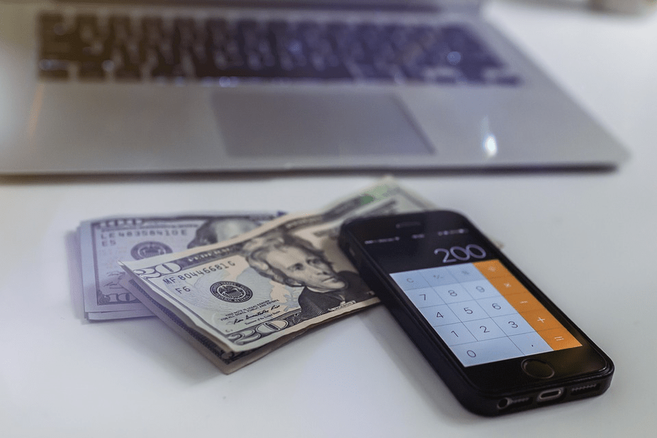 laptop with a pile of money and a mobile phone