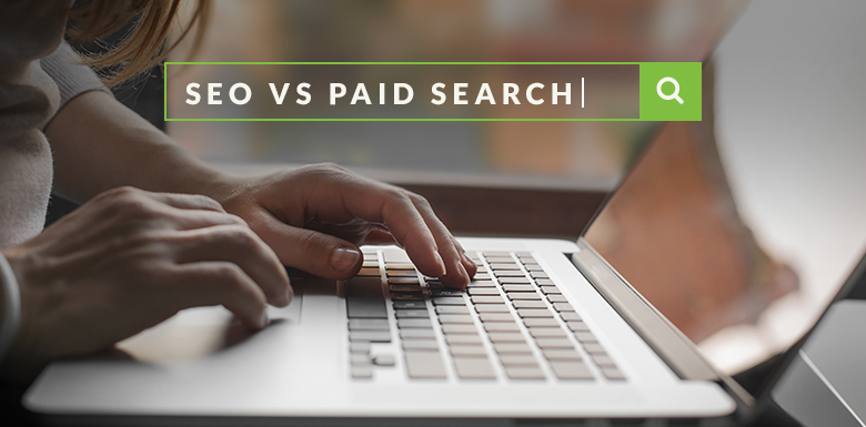 Person on laptop typing SEO vs. paid search