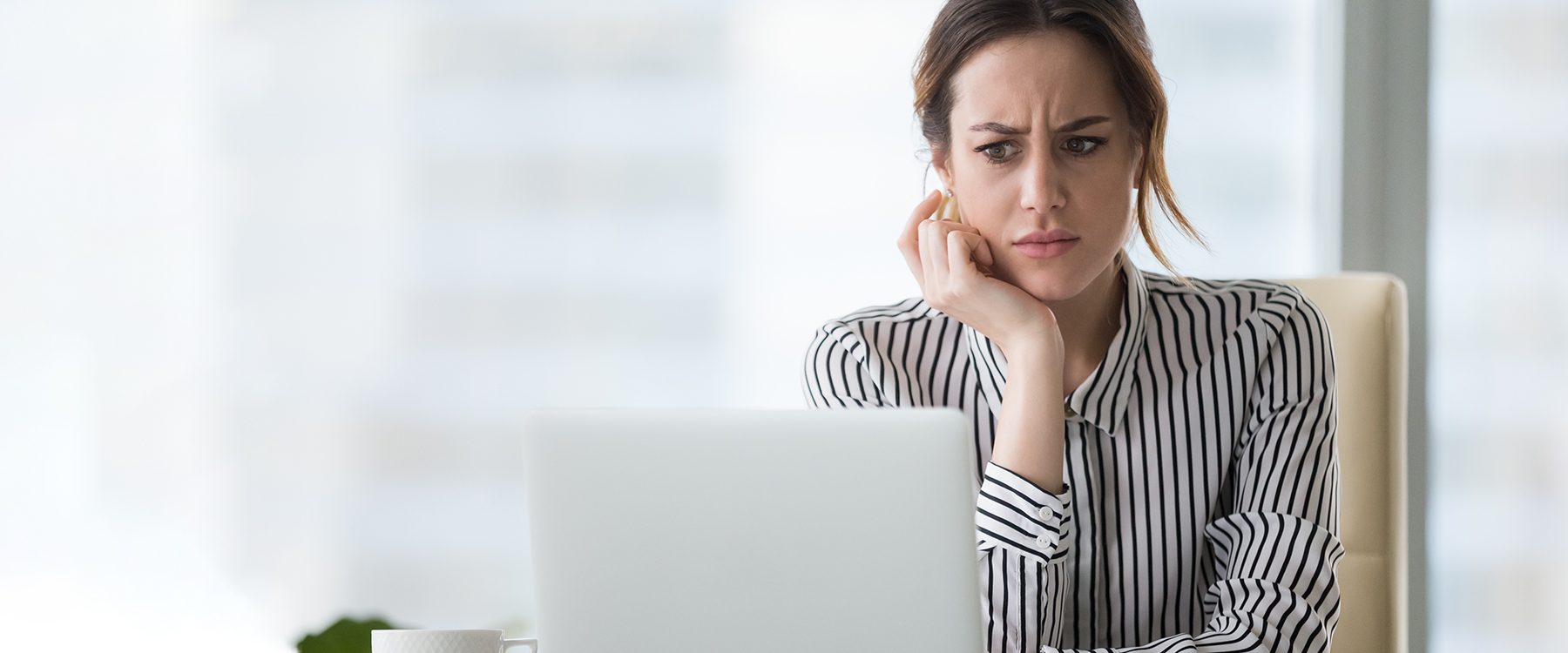 Woman disgruntled looking at old website design on laptop