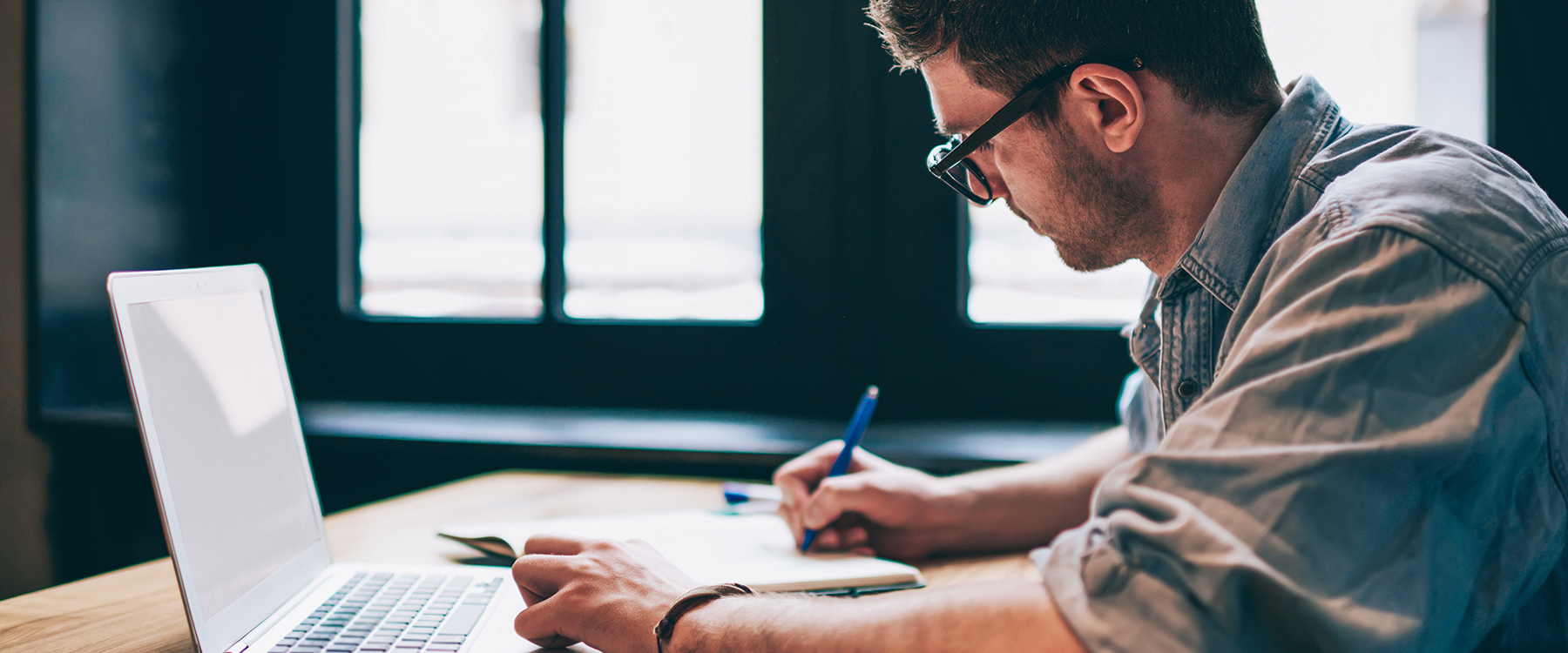 Man writing list of to dos while consulting laptop