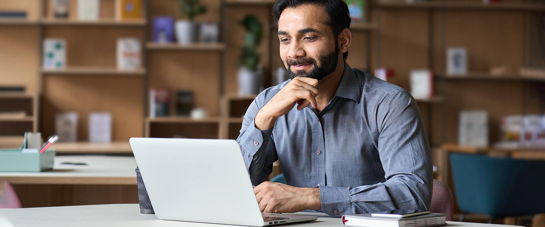 Man with beard and button up smiling at laptop in office