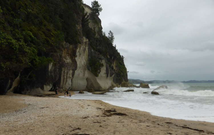 Lonely bay is a sweet sandy beach with trees and rocks not far out.