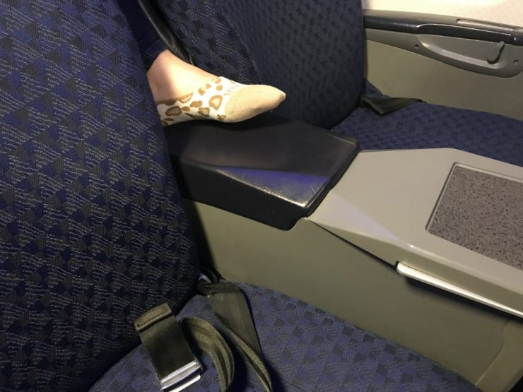 Foot between seats in first class.