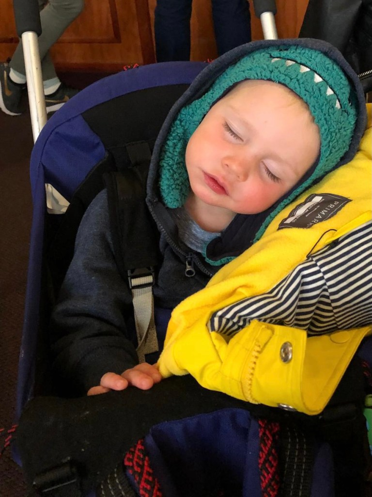 Sleeping child on the go. Traveling with kids.