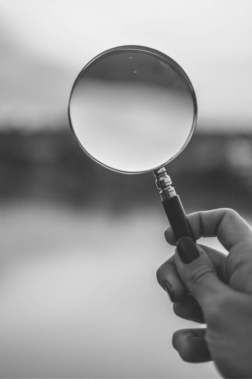 hand holding magnifying glass to symbolize self-discovery in the job-hunting process