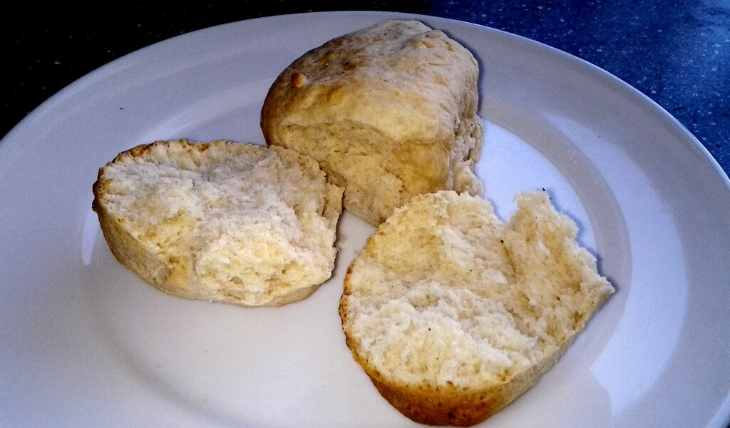 Two scones on a plate. One is broken open, ready for eating