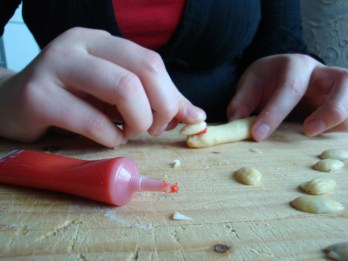 "Instead of rolling the dough into balls you shape finger size sticks out of them. You can fix a ""nail"" made out of half an almond glued on with either icing or red gel. You can make the joints if you run a knife over them while their are warm from the oven, where you want the joints."