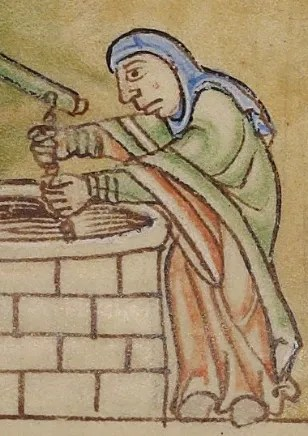 Woman getting water from a well. She is wearing a wide sleeved gown and a cape or mantle. She also wears a veil wrapped around her head like a hijab, c. 1155-1160