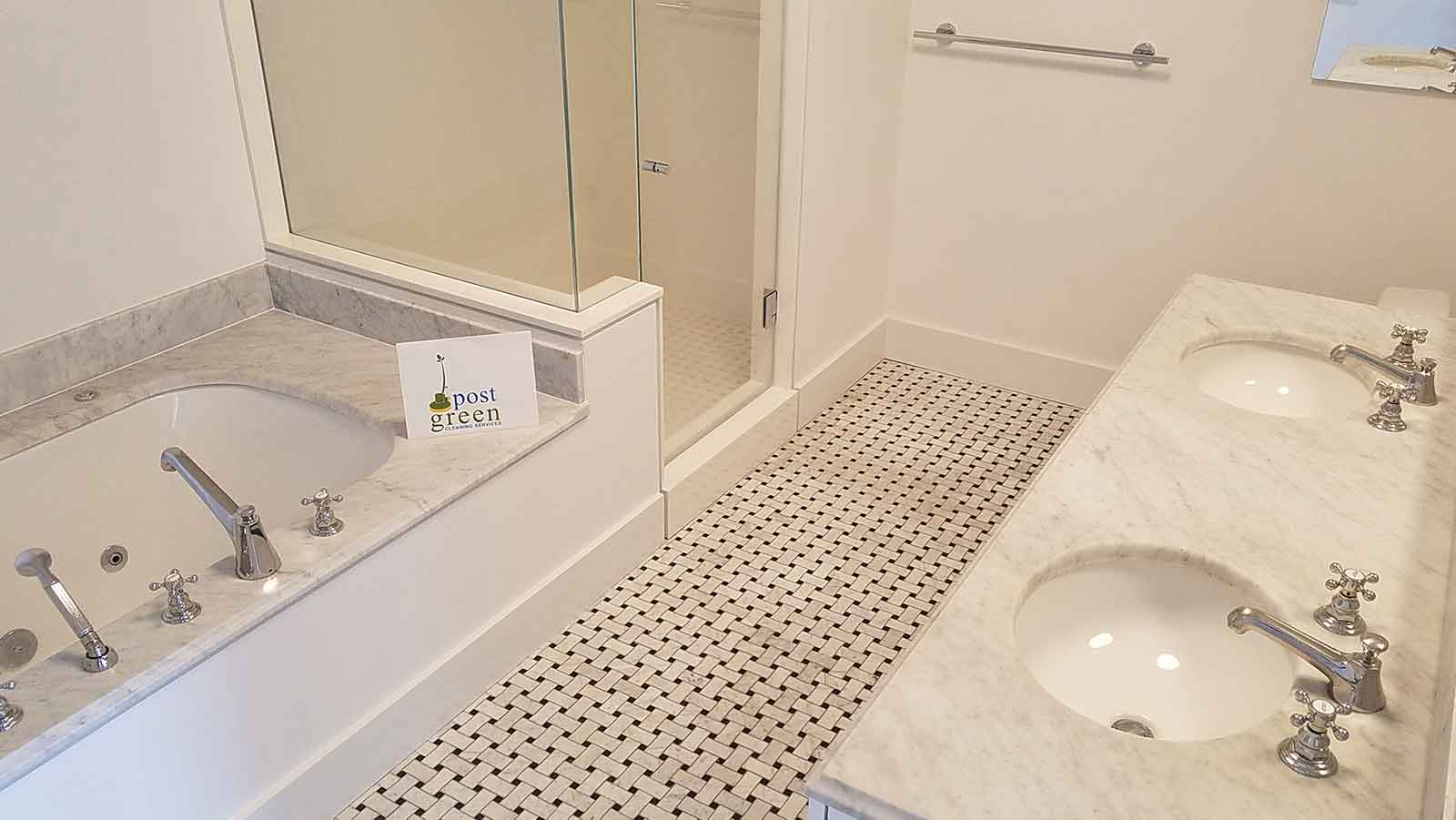 Marble bathroom vanity and tiled floor after post-construction cleaning.